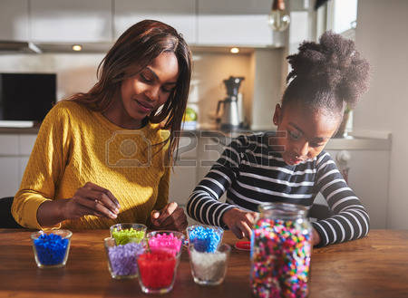 54382958-child-and-parent-sitting-and-creating-color-beaded-crafts-on-wooden-table-in-kitchen-with-various-ja